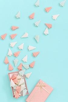 Пастельные милые конфетные конфеты в виде елок разбросаны по подарочной коробке.