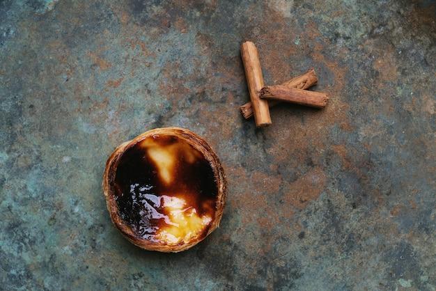 パステルデナタ。素朴な金属の背景の上に伝統的なポルトガルのデザートエッグタルトとシナモンスティック。上面図