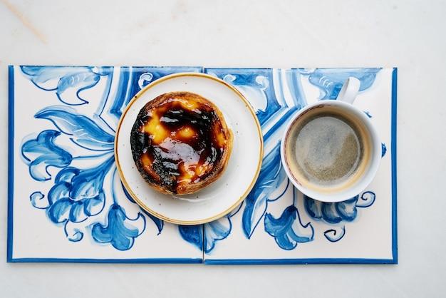 パステルデナタ。大理石の背景の上の伝統的なアズレージョタイルの伝統的なポルトガルのデザート、エッグタルトとコーヒーのカップ。上面図
