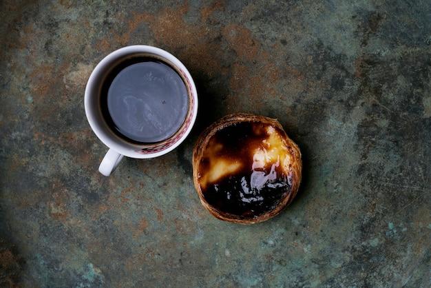 パステルデナタ。素朴な金属の背景の上に伝統的なポルトガルのデザートエッグタルトとコーヒーのカップ。上面図
