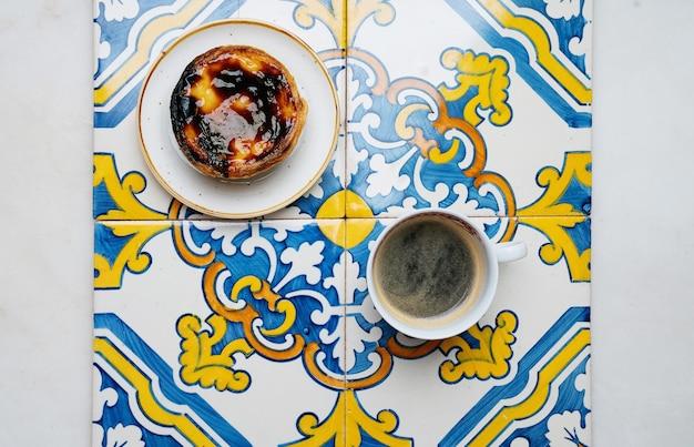 パステルデナタ。伝統的なポルトガルのデザート、エッグタルト、伝統的なアズレージョのタイルの上にコーヒーを一杯。上面図
