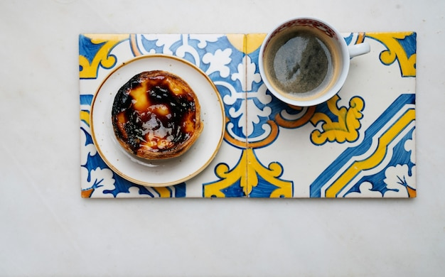 Pastel de nata. traditional portuguese dessert, egg tart and cup of coffee on traditional azulejo tiles over marble background. top view