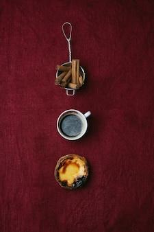 パステルデナタ。伝統的なポルトガルのデザート、エッグタルト、一杯のコーヒー、シナモンがテキスタイルの背景の上にストレーナーに刺さっています。上面図