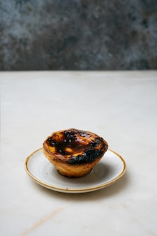 Pastel de nata. traditional portuguese dessert, egg tart over marble background in front of rustic metal background. selective focus