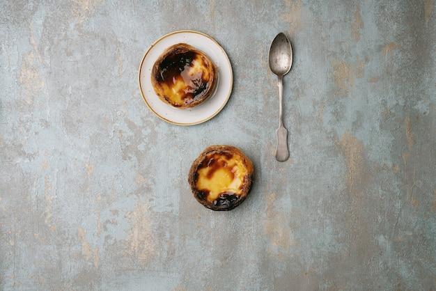パステルデナタ。伝統的なポルトガルのデザート、プレートと素朴な背景の上にエッグタルト。上面図