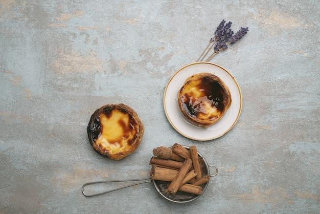 パステルデナタ。伝統的なポルトガルのデザート、素朴な背景の上のプレート上のエッグタルト、ストレーナーのシナモンスティック、乾燥したラベンダーの小枝。上面図