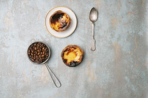 パステルデナタ。伝統的なポルトガルのデザート、プレート上のエッグタルト、素朴な背景の上にローストしたコーヒー豆をストレーナーに入れます。上面図