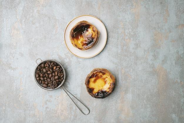 パステルデナタ。伝統的なポルトガルのデザート、プレート上のエッグタルト、素朴な背景の上に、ストレーナーに焙煎したコーヒービンがあります。上面図