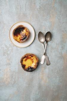 パステルデナタ。伝統的なポルトガルのデザート、プレート上のエッグタルトと素朴な背景の上にスプーン2杯。上面図