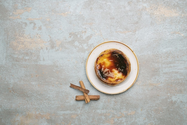 パステルデナタ。伝統的なポルトガルのデザート、シナモンスティックで素朴な背景の上にプレート上のエッグタルト。上面図