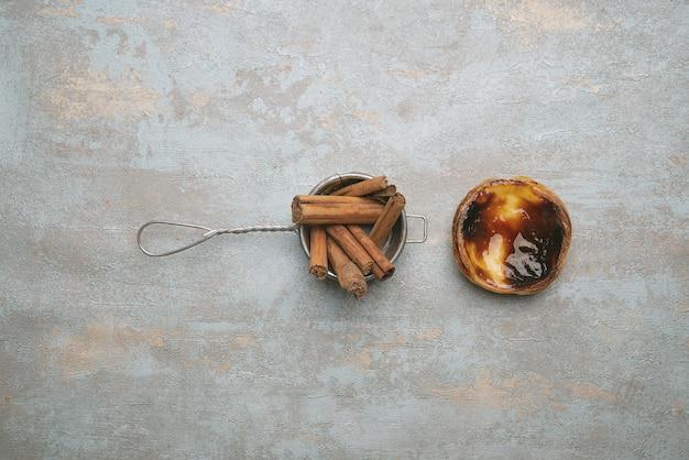 パステルデナタ。伝統的なポルトガルのデザート、素朴な背景にエッグタルト、ストレーナーにシナモンスティック。上面図