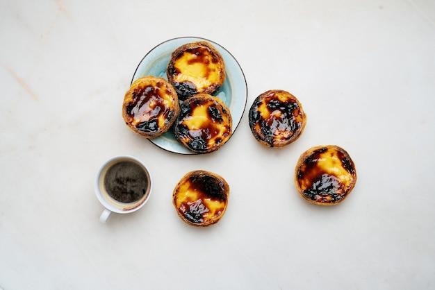パステルデナタ。伝統的なポルトガルのデザート、大理石の背景の上にコーヒーのカップとエッグタルト。上面図