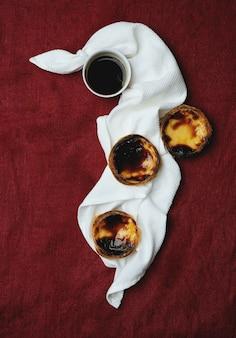 パステルデナタ。伝統的なポルトガルのデザート、エッグタルト、テキスタイルの背景の上のナプキンのコーヒーのカップ。上面図