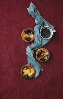 パステルデナタ。ナプキンで飾られたテキスタイルの背景の上に伝統的なポルトガルのデザート、エッグタルトとコーヒーのカップ。上面図