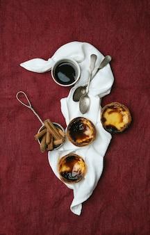 パステルデナタ。伝統的なポルトガルのデザートエッグタルト、一杯のコーヒー、シナモンスティックがテキスタイルの背景の上のナプキンのストレーナーにあります。上面図