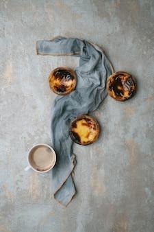 パステルデナタ。伝統的なポルトガルのデザート、素朴な背景の上のエッグタルト、ナプキンで飾られた一杯のコーヒー。上面図