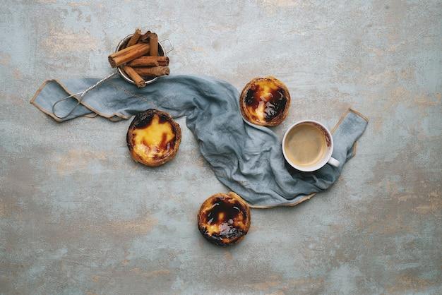パステルデナタ。伝統的なポルトガルのデザート、素朴な背景にエッグタルト、ストレーナーにシナモンスティック、ナプキンで飾られたコーヒー。上面図