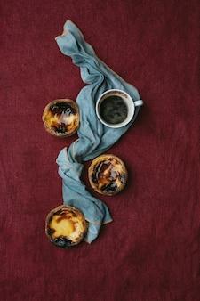 パステルデナタ。伝統的なポルトガルのデザート、テキスタイルの背景にエッグタルト、ナプキンで飾られた一杯のコーヒー。上面図