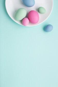 복사 공간와 파란색 배경에 접시에 파스텔 부활절 달걀.