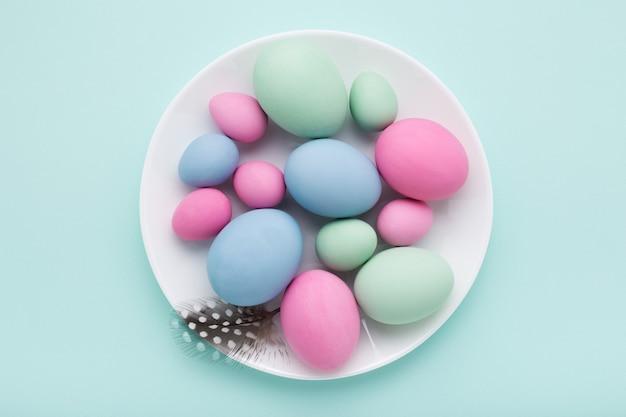 파란색 배경에 흰색 접시에 파스텔 부활절 달걀.