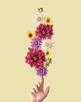 パステルカラーの花が指に調和してバランスを取ります。トレンドの現代的な安定性の概念