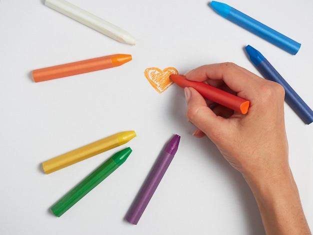 Пастельное сердце на листе бумаги. разноцветные пастельные мелки лежат на белой бумаге
