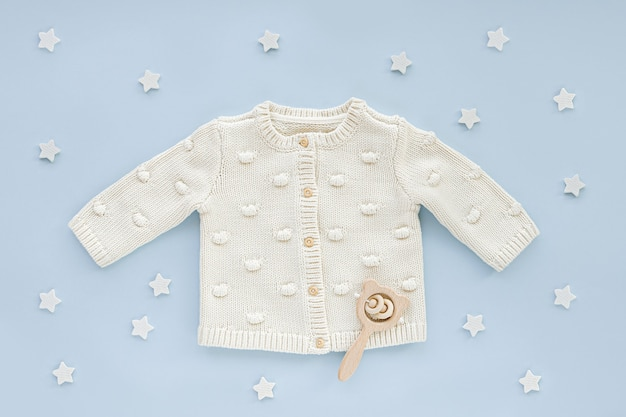 Pastel knitted jumper  and  wooden rattle. cute set of baby clothes and accessories  blue background with stars.  fashion newborn for boy. flat lay, top view
