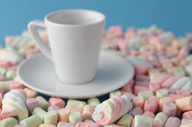 パステルマシュマロと青色の背景に白いカップ