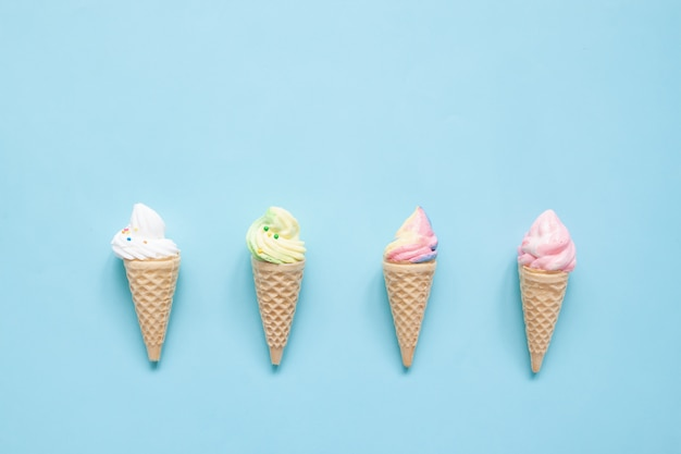 Pastel meringue on ice cream cones on blue background