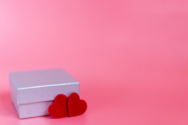 Pastel pink background with a silver gift box and two craft little red heart shape decorate for someone special