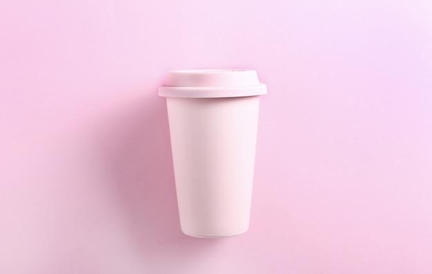 Pastel pink ceramic travel mug on pink. top view, flat lay. tumbler cup on pink.