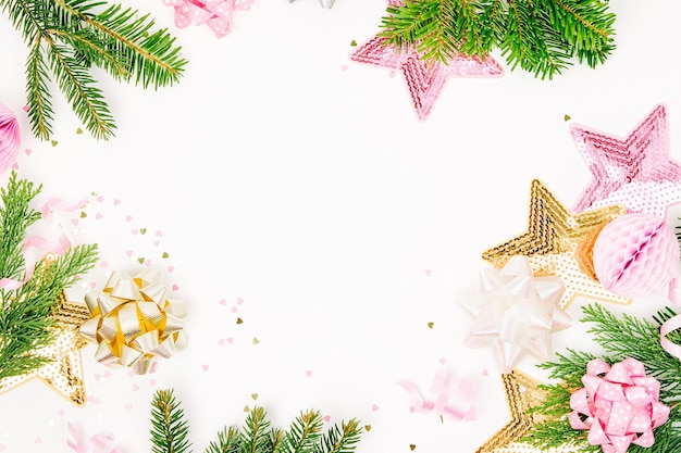 Пастельно-розовые конфетти, банты и бумажные украшения. плоская планировка, вид сверху. праздничная композиция для празднования нового года или рождества. плоская планировка, вид сверху
