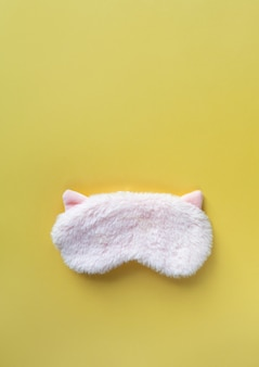 Pastel pink fluffy fur sleep mask with small ears on pastel yellow paper background. top view, flat lay, copy space. concept of vivid dreams. accessories for girls and young women