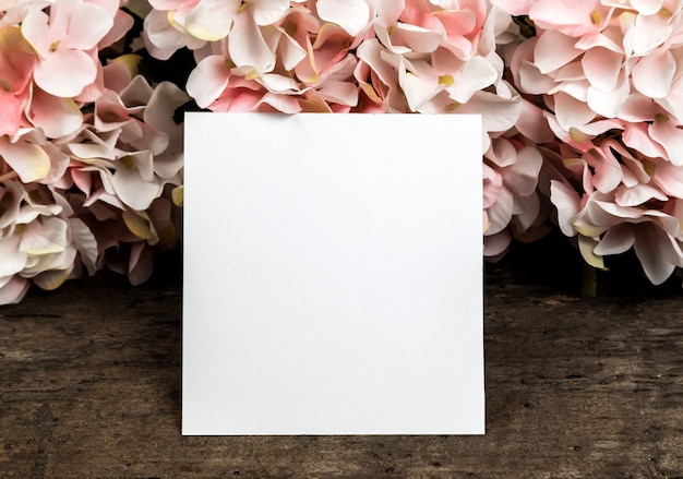 Pastel pink hydrangea flowers and a piece of paper on wood . copyspace for text
