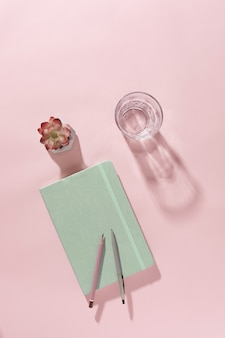 Пастельный розовый офисный фон с закрытой зеленой записной книжкой, стаканом пресной воды с тенью, цветком и ручкой в концепции бизнеса, творчества или личного дневника