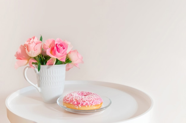Pastel pink roses in white cup with pink donut on white coffee table