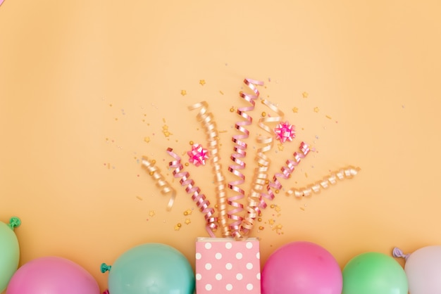 Pastel pink table with frame from balloons and confetti for birthday top view