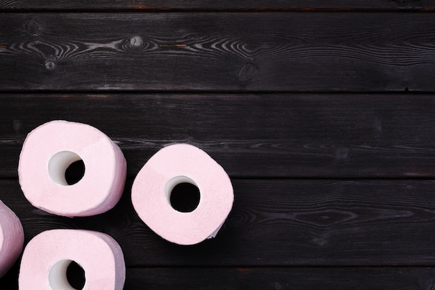 Pastel pink toilet paper rolls on black wooden table