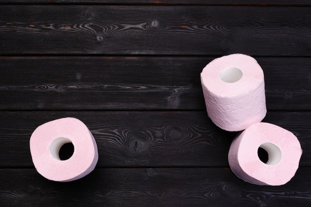 Pastel pink toilet paper rolls on black wooden