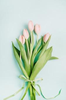 淡い青の背景にパステル ピンクのチューリップの花の花束。フラットレイ、トップビュー