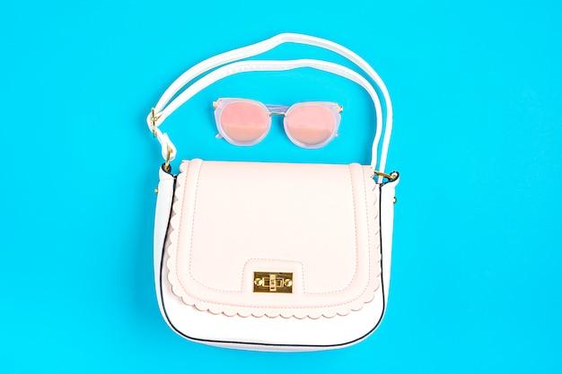 Пастельно-розовая, белая сумка, солнцезащитные очки на синей поверхности flat lay