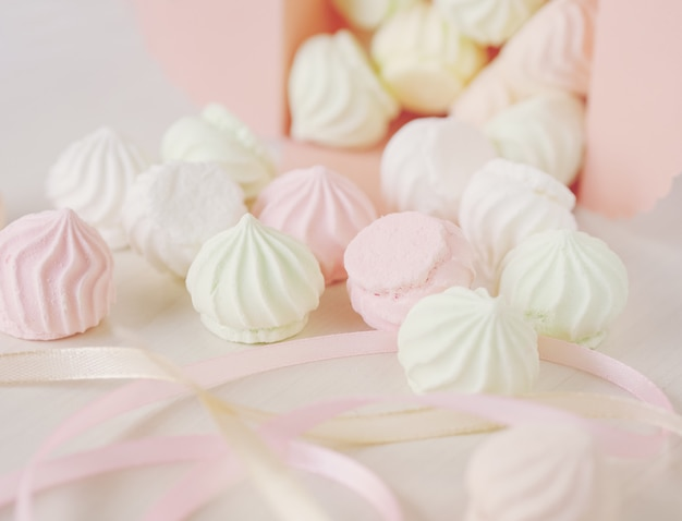 Pastel romantic background with small meringues in a box
