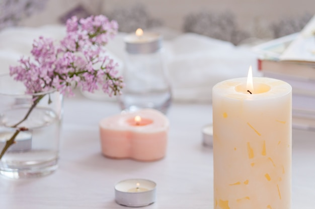 Pastel room interior decor with burning hand-made candle, books, flowers. cozy and relax concept.