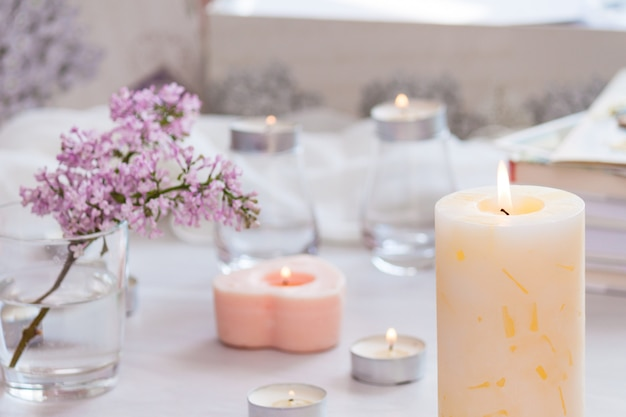 Pastel room interior decor with burning hand-made candle, books, flowers.