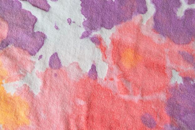 Пастельная краска для галстука, узор ручной работы на хлопковой футболке. крупный план, вид сверху.