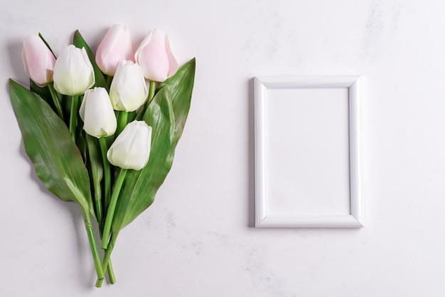 Pastel tulips with blank picture frame on white marble background, copy space