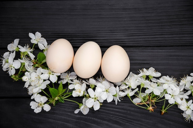 暗い木製の背景に桜の花の枝とパステル無着色イースターエッグ。花の枝を持つ天然卵。イースターホリデー。花の春の装飾。コピースペース、上面図、フラットレイ