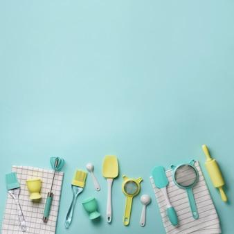 ターコイズブルーの背景にパステル調の黄色、青の調理器具。食品成分。ケーキを調理し、パンを焼くコンセプト。