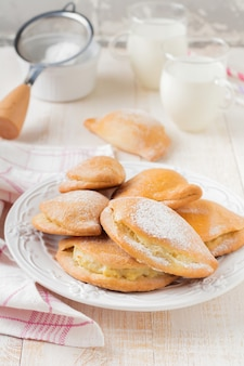 Pasties with cottage cheese and powdered sugar on a light wooden surface