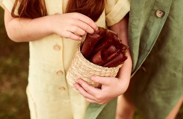 Пастила и клубника в руках молодой женщины, одетой в зеленое льняное платье в поле